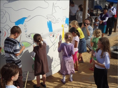 Children_painting_mural_on_bom
